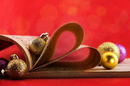 music notation: Music notation book with pages shaping heart and Christmas ornaments with bokeh lights Stock Photo