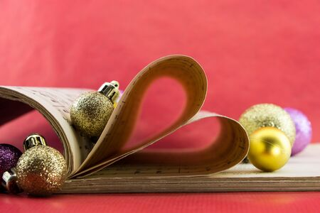 notation: Music notation book with pages shaping heart and Christmas ornaments