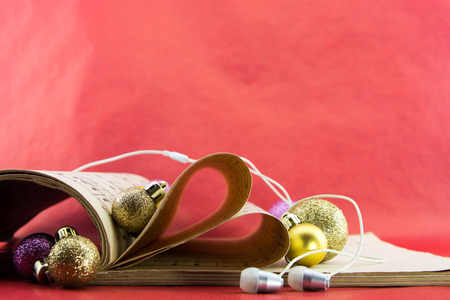 notation: Music notation book with pages shaping heart with earphones and Christmas ornaments
