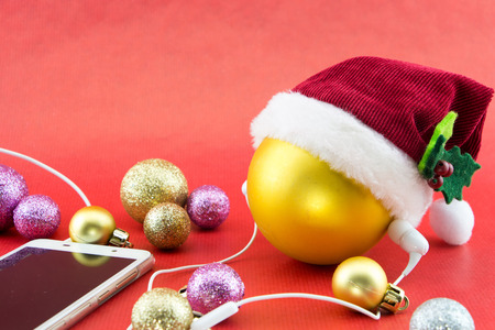 Christmas ball with Santas hat and smartphone with earphones, on red with copy-space