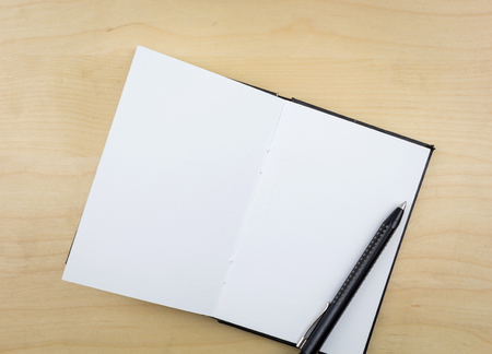 notebook: Open notebook with black pen, on wooden surface. Stock Photo