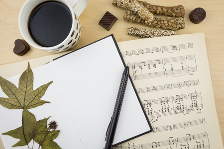 notation: Opened blank notebook with pen, cup of coffee and music notation book, on wooden desktop. Stock Photo