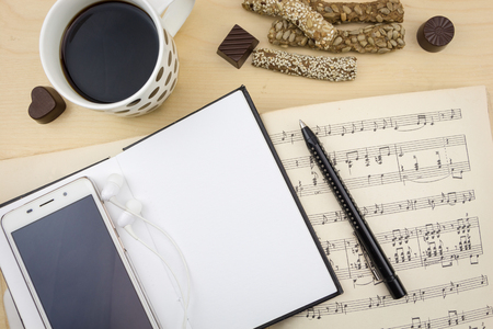 notation: Opened blank notebook with smartphone, pen, cup of coffee and music notation book, on wooden desktop.