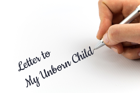 unborn: Hand writing Letter to My Unborn Child on white sheet of paper.