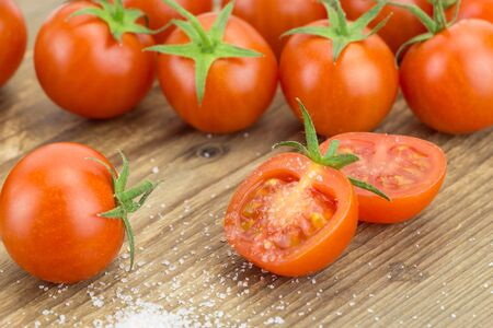pinch: Heap of cherry tomatoes with one cut in half and pinch of salt, on wooden surface.