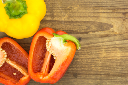 wooden surface: Fresh red and yellow bell peppers, on wooden surface