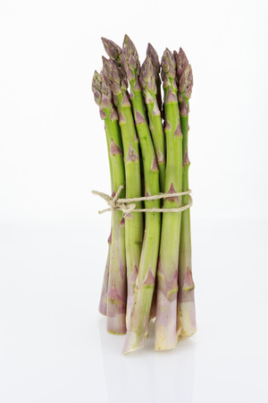 Bunch of asparagus tied with raffia cord, isolated on white background.