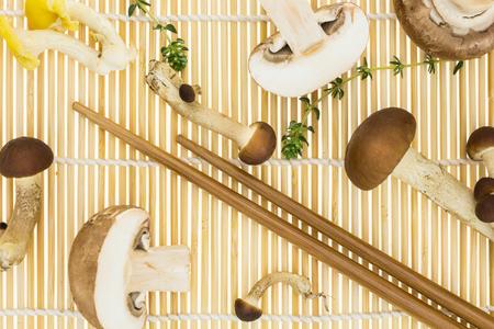 chop sticks: Chop sticks with bunch of mushrooms, on bamboo mat