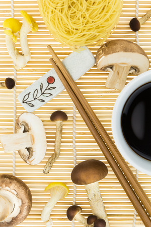chop sticks: Chop sticks with bunch of mushrooms and dry noodles nests, on bamboo mat