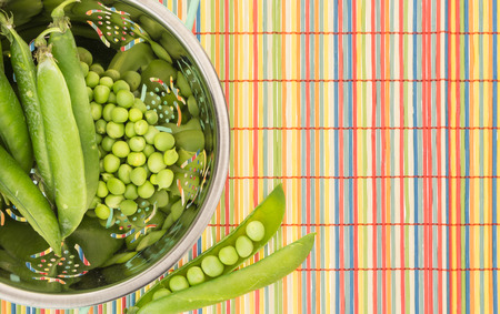 colander: Fresh green peas in colander, on colorful bamboo placemat