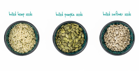 hulled: Hulled hemp, pumpkin and sunflower seeds in bowls, on white background