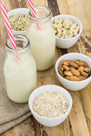 is based: Bottles of homemade plant based milk and bowls with ingredients, on wooden background