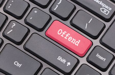 offend: Computer keyboard closeup with Offend text on red enter key