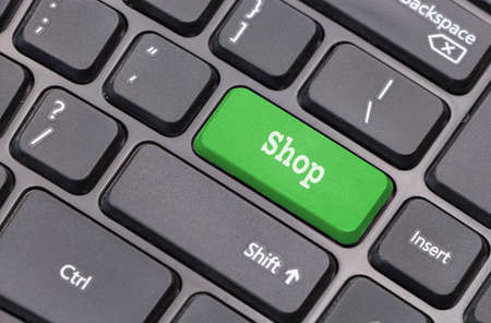 enter key: Computer keyboard closeup with Shop text on green enter key Stock Photo