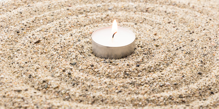 scent: Scent lighted candle on sand imitating water ripples Stock Photo