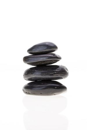 Stack of black basalt balancing stones, on white background.