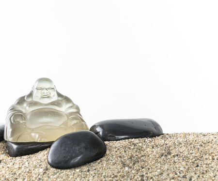 smiling buddha: Glass smiling Buddha with stones on sand,  on white background.