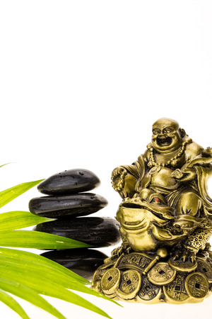 Laughing Buddha and stack of black basalt stones, on white background.