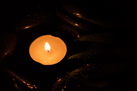 scent: Scent lighted candle on black wet stones, dark photography