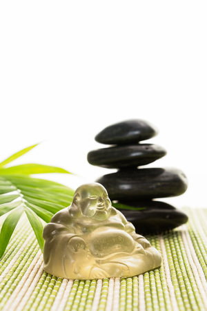 smiling buddha: Glass smiling Buddha with stones and leaves on bamboo mat, isolated on white background.