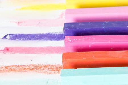 Mazzo di quadrati colorati pastelli e loro pigmenti colorati, su sfondo bianco