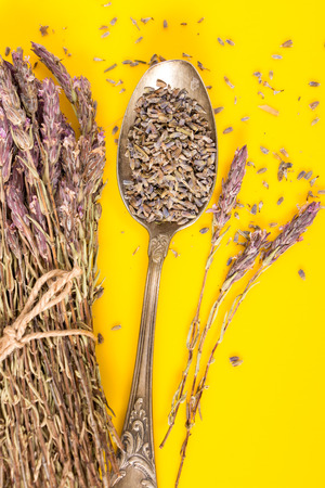 Lavender bundle and dried lavender on antique spoon, with vivid yellow background.