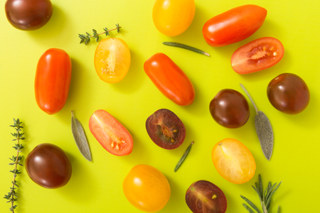chartreuse: Colorful cherry tomatoes with herbs, on chartreuse yellow background.
