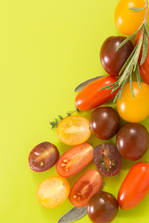 chartreuse: Colorful cherry tomatoes cluster with herbs, on chartreuse yellow background with copy-space