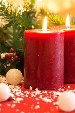Lit red candles with Christmas tree branch and balls , on red fabric.