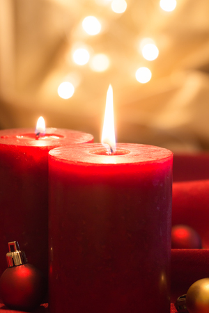 Lit red candles with Christmas balls , on red wavy fabric and golden background with bokeh.