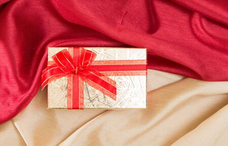 Gift box with bow, on red and golden wavy satin fabrics.