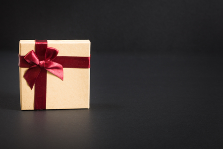 Paper gift box with deep red ribbon and a bow, on black background.