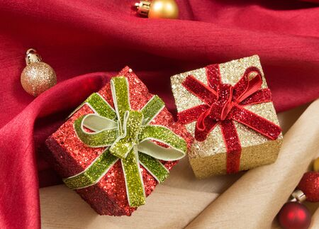 Two gift boxes with bows, on red and golden wavy satin fabrics with Christmas balls. Stock Photo