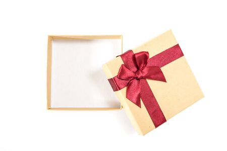 Paper gift box with deep red ribbon with a bow, on white background.