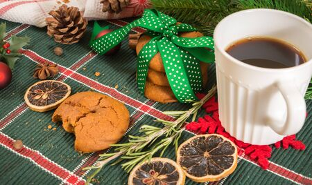 Cookies tied with green ribbon and coffee with Christmas decoration, on wooden surface. Stock Photo