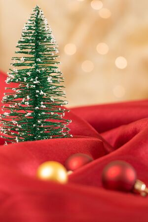 Christmas tree ornament, on red wavy fabric with golden bokeh background. Stock Photo