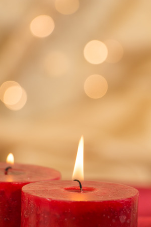 Lit red candles closeup and golden background with bokeh.