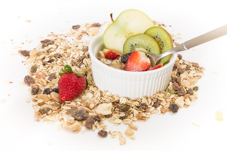 Bowl of muesli with fresh fruits and plant milk, on white background.