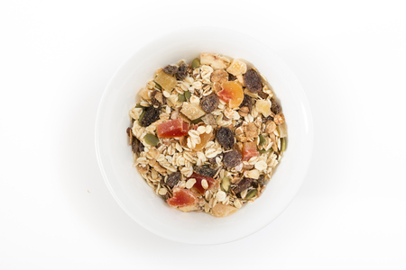 Bowl of muesli with dry fruits, on white background.