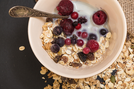 Bowl of muesli with frozen berries and plant milk, on black background. Stock Photo