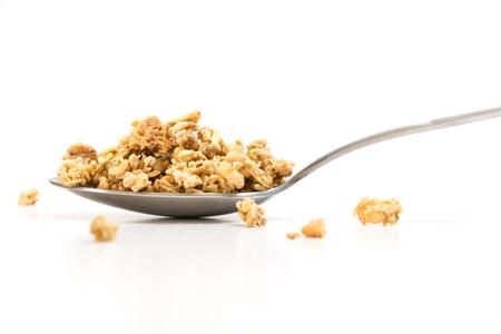 Spoon with granola, on white background. Stock Photo