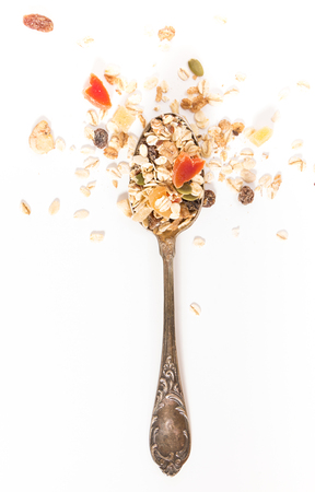 Spoon with muesli and dry fruits, on white background.