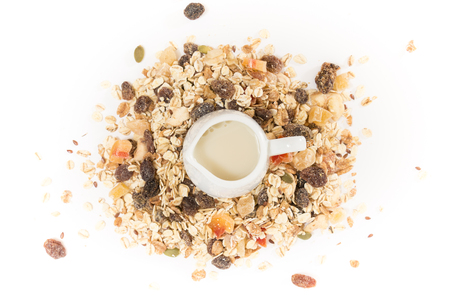 White milk pot with plant milk, on pile of muesli with dry fruits, on white background. Stock Photo