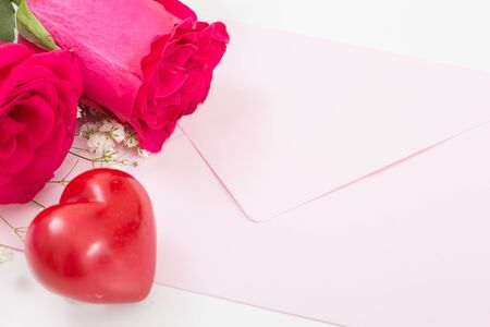 Red heart with pink envelope and red roses closeup.