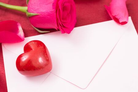 Red heart with pink envelope and red rose and petals closeup.