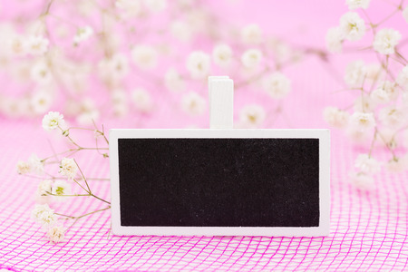 Closeup of blank blackboard sign with white flowers, on pink background and copy-space. Stock Photo