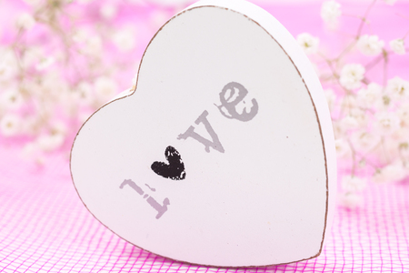 White wooden heart closeup with word Love, on pink mesh fabric and white flowers blurred background. Stock Photo