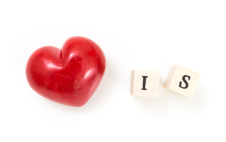 Red heart and wooden cubes with word Is, on white background. Love is concept.