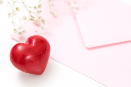 Closeup of a red heart with pink envelope and white flowers.