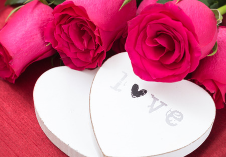 Closeup of two white wooden hearts and roses bouquet, on red fabric background.